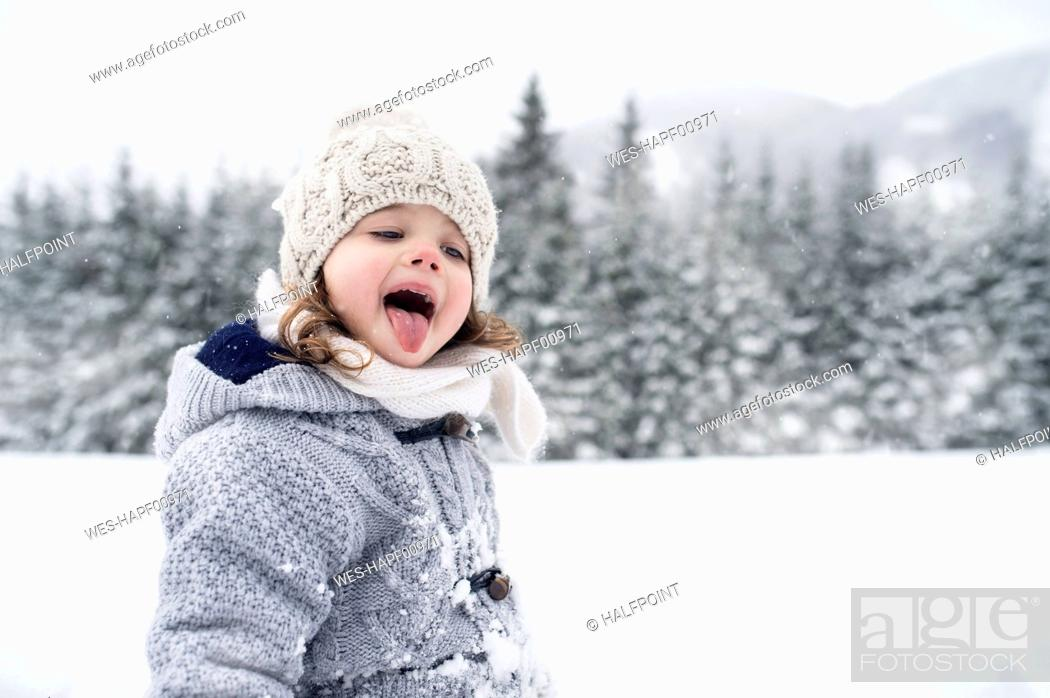 Photo de stock: Girl in winter landscape catching snowflakes with her tongue.