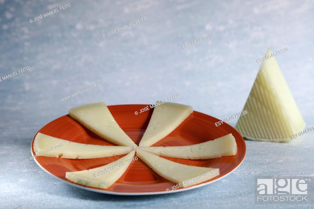 Stock Photo: six slices of typical spanish manchego cheese on red ceramic plate and piece manchego cheese on blue background. Copy space.
