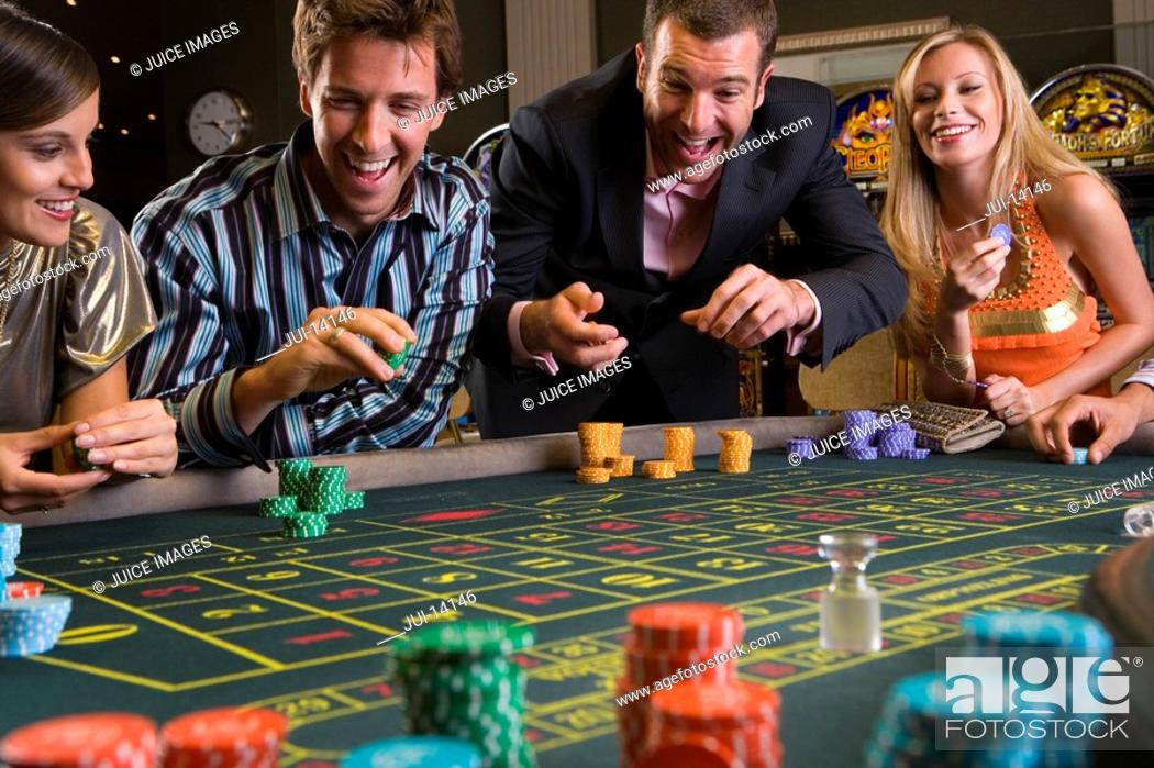 Stock Photo: Men and women gambling at roulette table in casino, smiling.