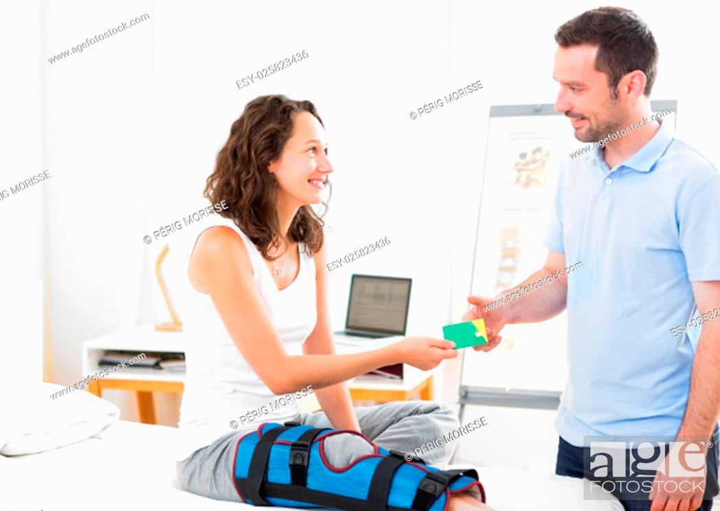 Stock Photo: View of a Young attarctive woman giving healthcare card to physiotherapist.