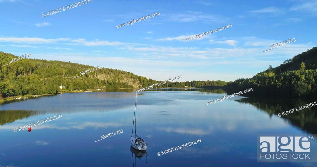 Stock Photo: Sailing yacht moored in a glassy bay of the Baltic Sea at the Swedish High Coast (Höga Kusten)on a sunny summer day. Aerial shot.