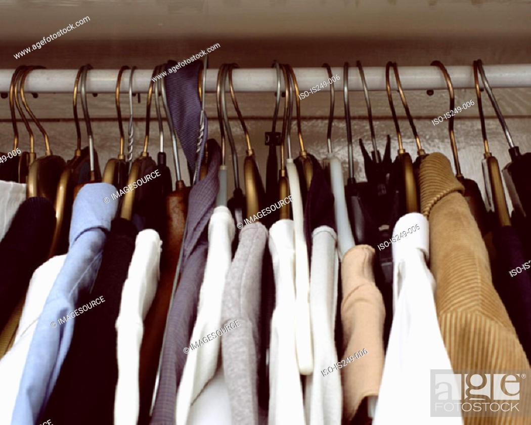 Stock Photo: Clothes hanging in cupboard.
