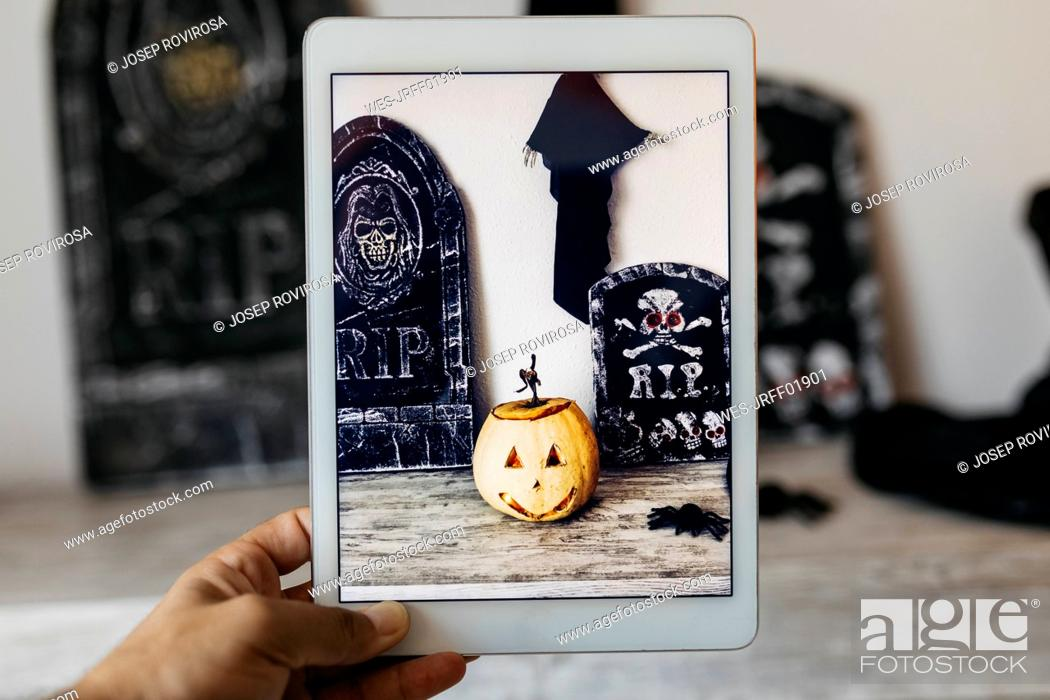 Stock Photo: Man taking photo of Halloween decoration with digital tablet.