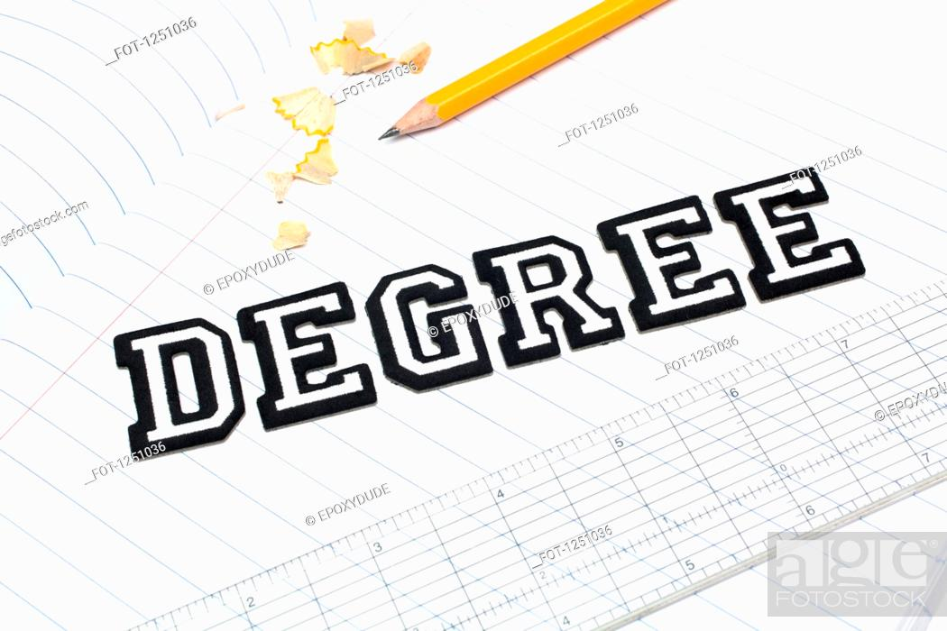 Stock Photo: Varsity font stickers spelling out Degree atop a lined paper notebook with ruler and pencil.