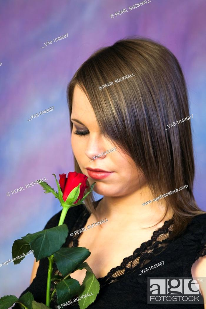 Stock Photo: Studio, UK, Europe  Young woman smelling a red rose.