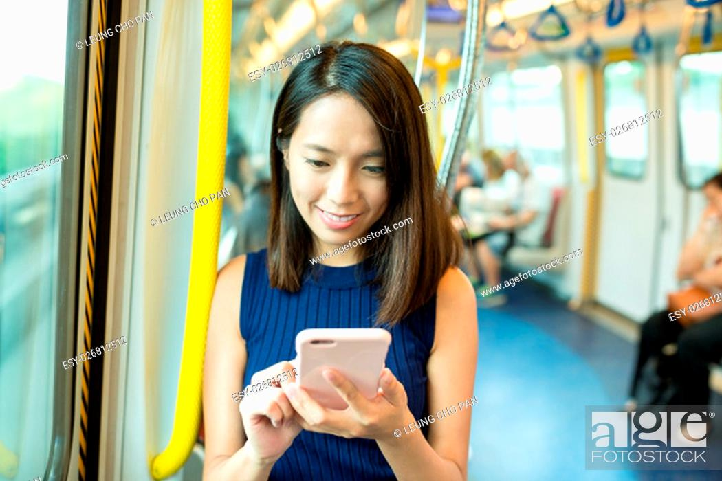 Stock Photo: Woman using cellphone inside MTR in Hong Kong.