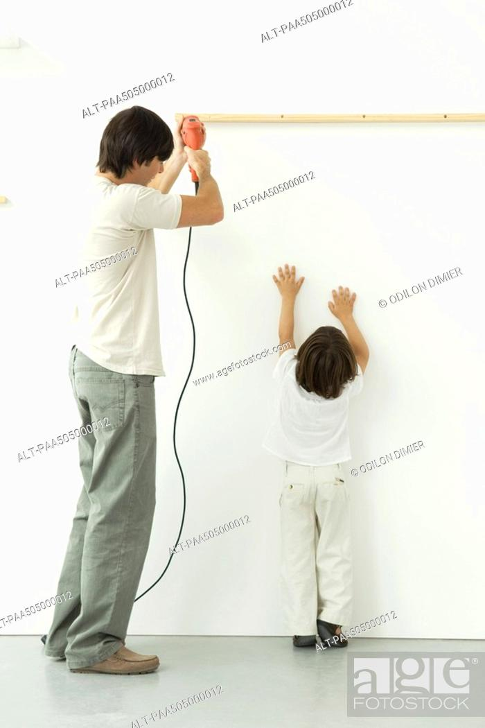 Stock Photo: Man drilling into wall, his son reaching up, trying to help.
