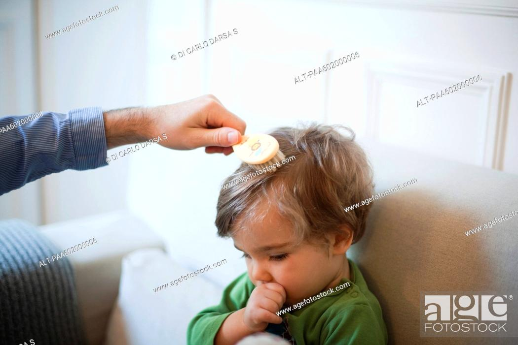 Stock Photo: Father brushing toddler son's hair, cropped.