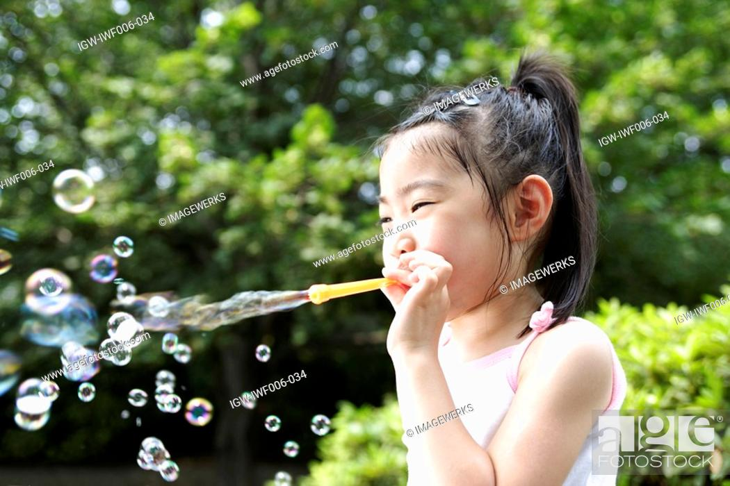 Stock Photo: A girl blowing bubbles.