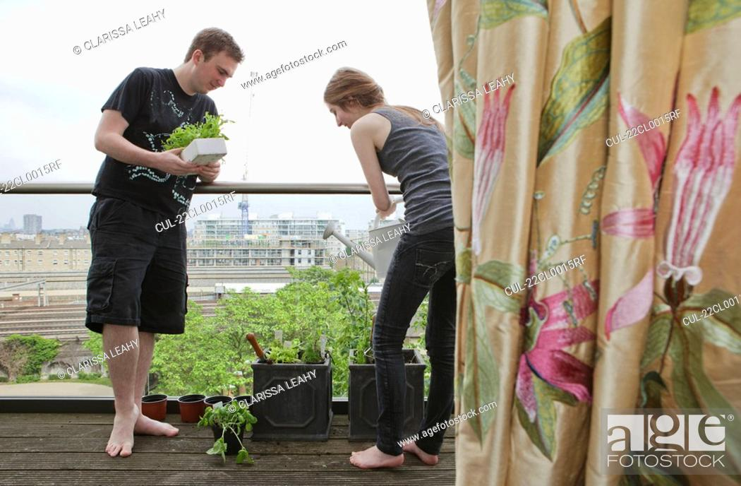 Stock Photo: Man and woman planting up flower pots.