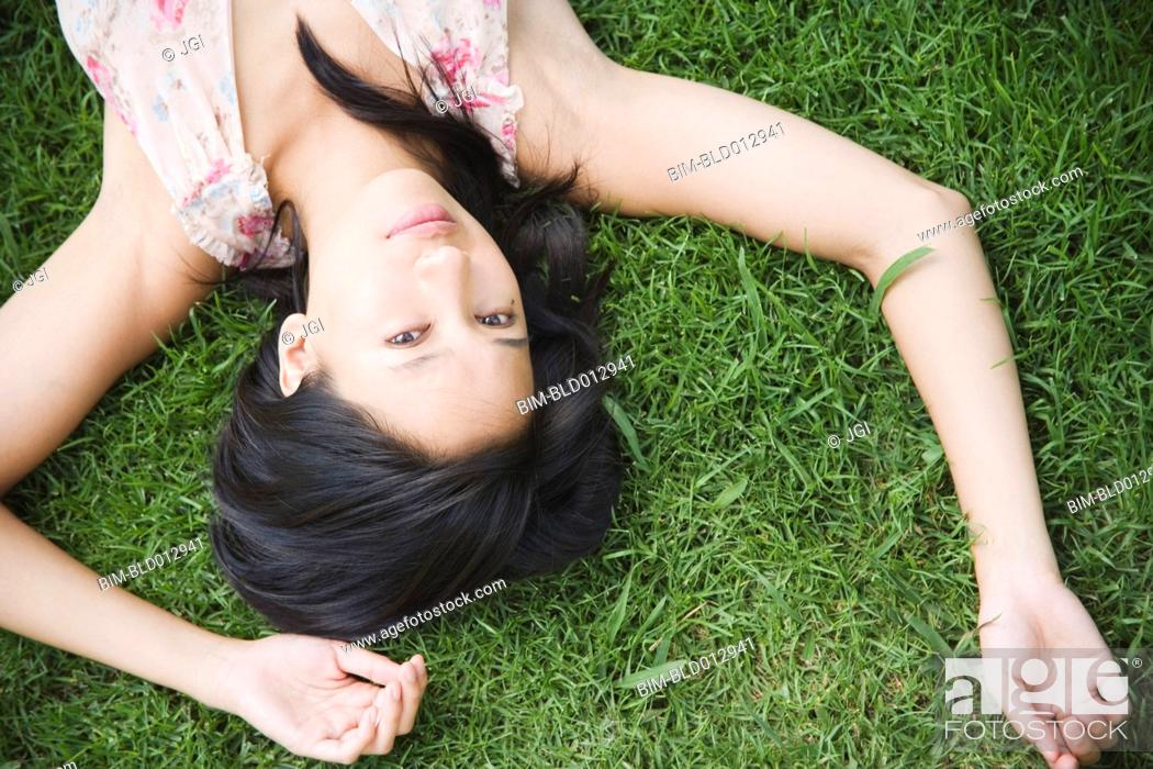 Stock Photo: Portrait of woman laying in grass with arms over head.