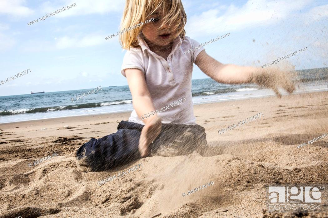 Stock Photo: Young Boy Playing with Sand on Beach.