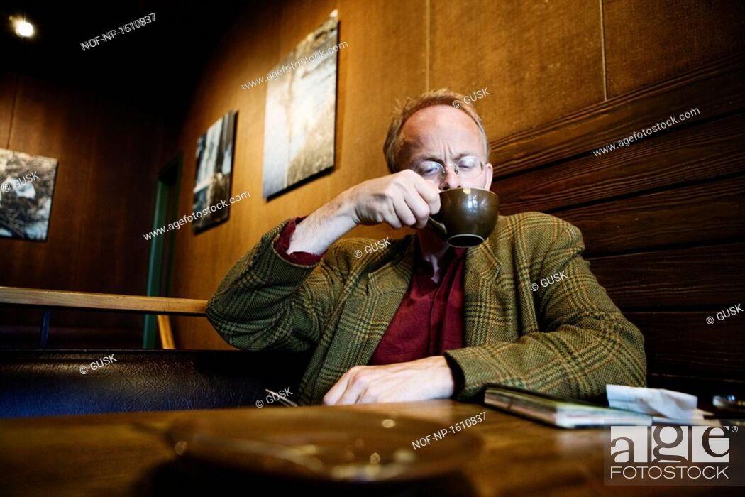 Stock Photo: Mature man drinking coffee in a cafe.