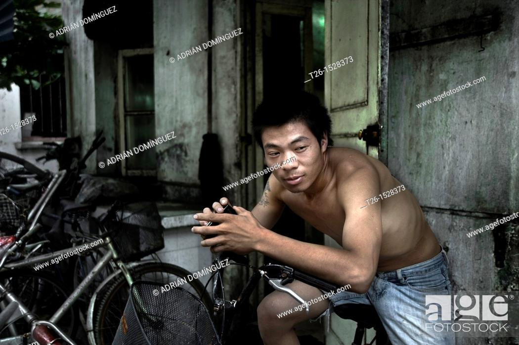 Stock Photo: Man on his bicke in Shanghai Old city. China country.