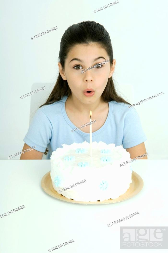 Imagen: Girl blowing out candle on birthday cake, portrait.