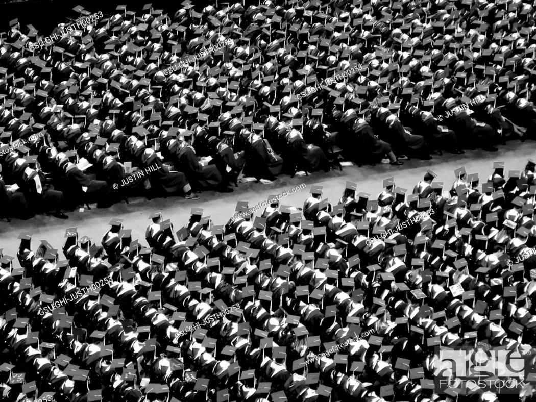 College Graduates Sitting At Graduation Ceremony Stock Photo