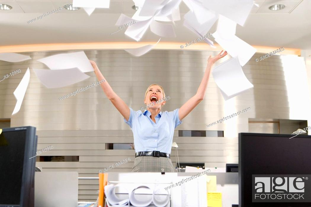 Stock Photo: Businesswoman throwing paper up in office, arms raised, smiling, low angle view.