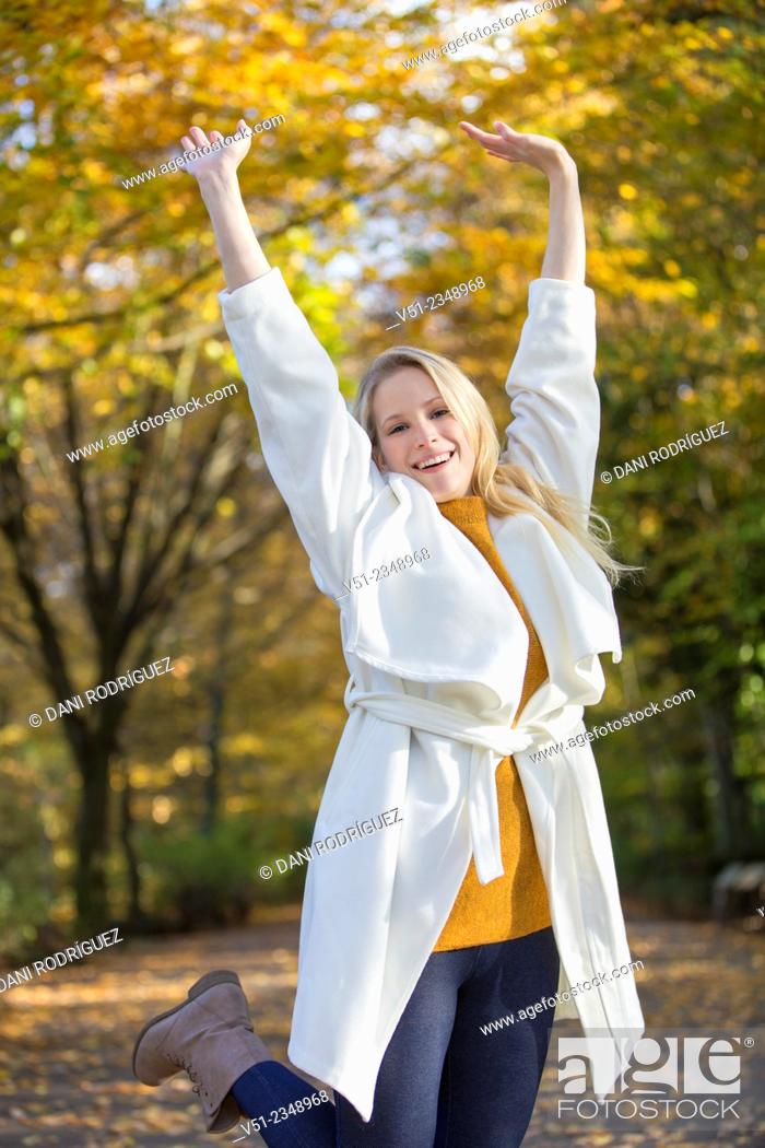 Stock Photo: Pretty blonde young woman walking in Park and smiling at camera with arms raised.