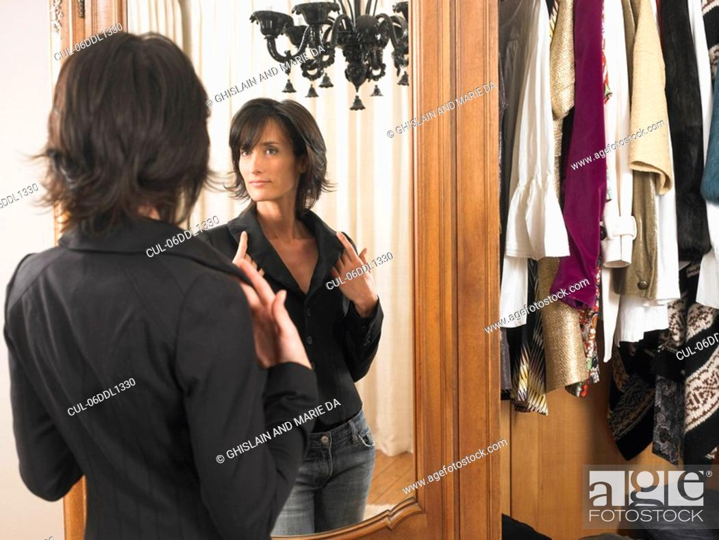 Stock Photo: Woman looking at herself in the mirror.