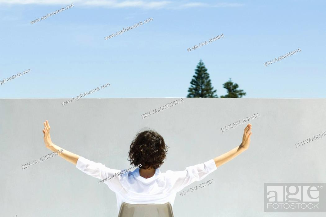 Stock Photo: Woman sitting outdoors, arms raised in the air, rear view.