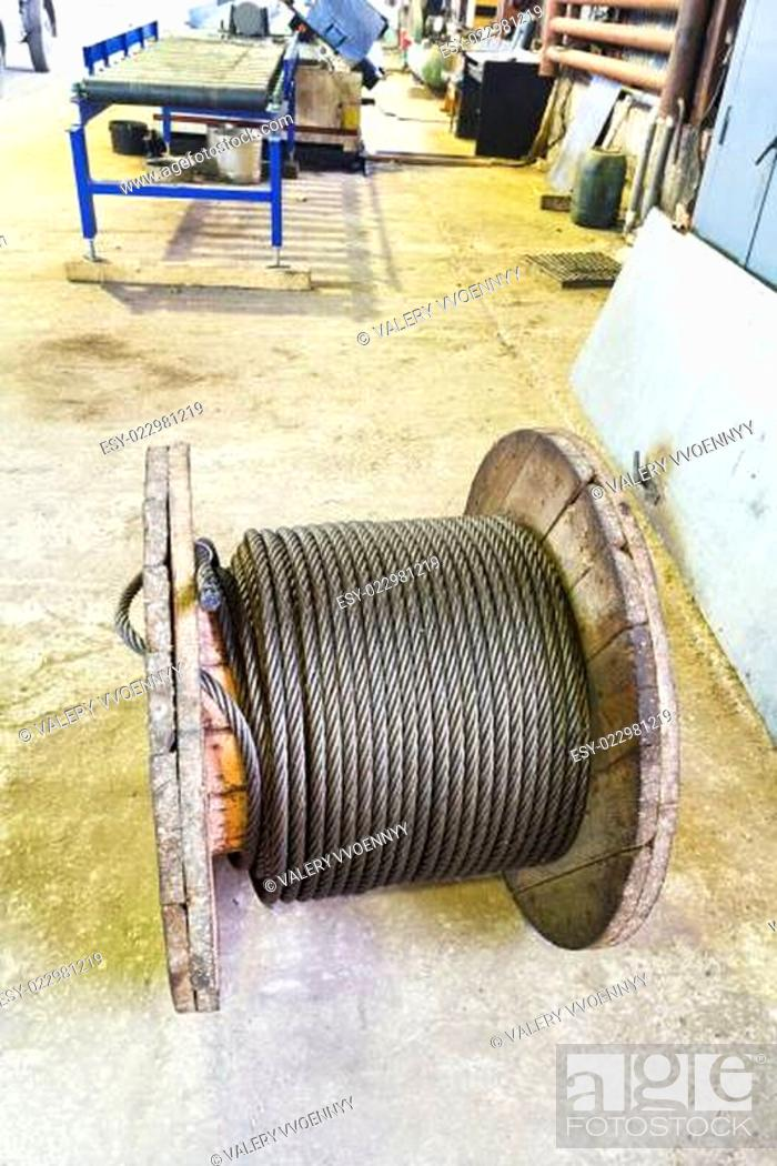 Stock Photo: wooden reel with steel rope in mechanical shop.