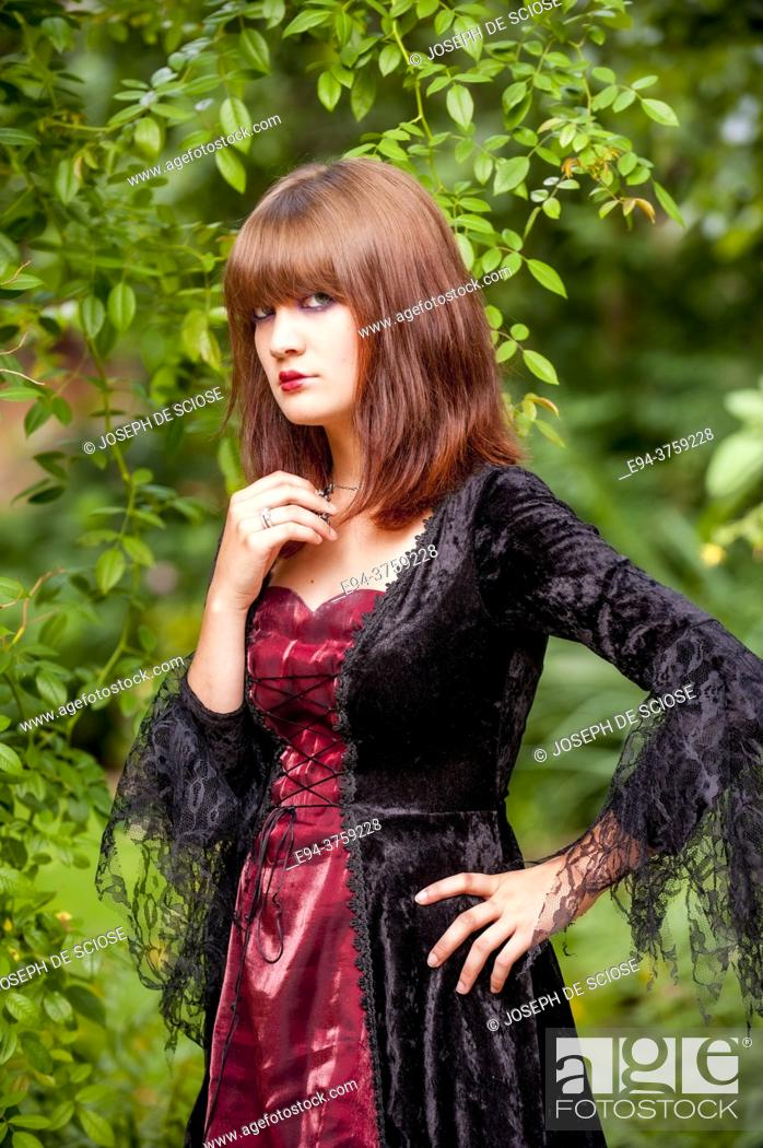 Stock Photo: An 18 year old brunette woman wearing a costume in a garden setting looking directly at the camera.