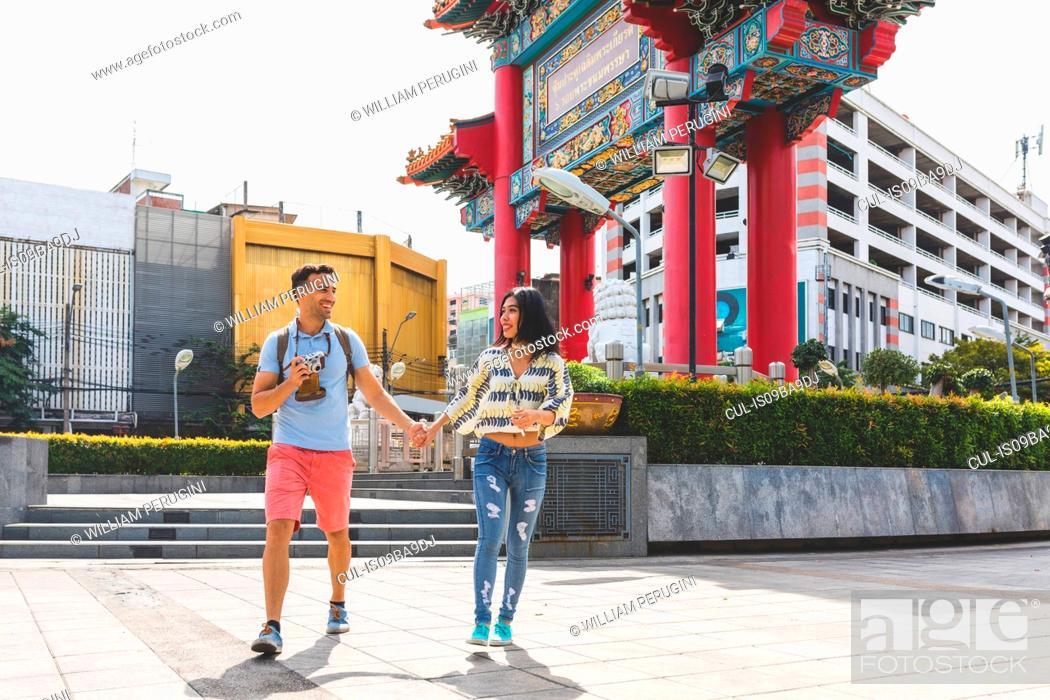 Stock Photo: Young tourist couple walking on sidewalk, Bangkok, Thailand.