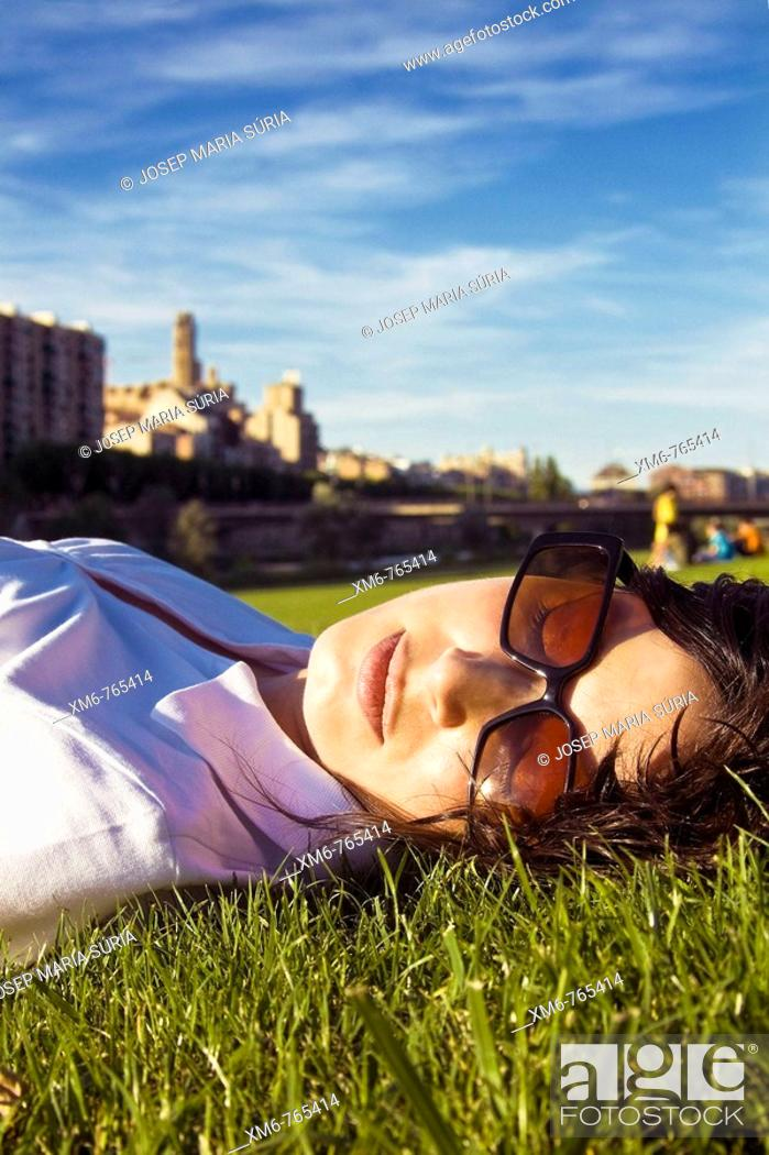 Stock Photo: Girl resting and enjoying the last lights of the afternoon at the side of the river. Total relaxation.