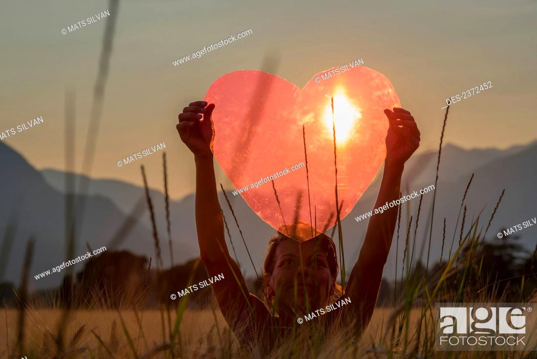 Stock Photo: A Woman Holds Up A Red Heart With The Sun To Shine Through; Locarno, Ticino, Switzerland.