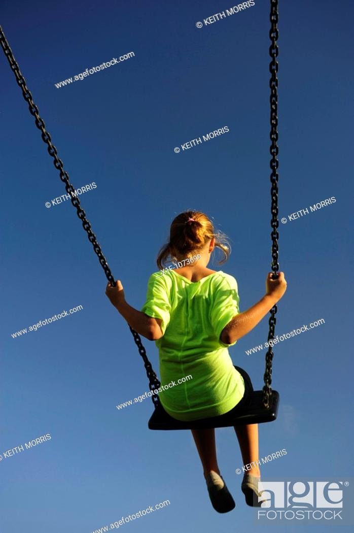 Stock Photo: Young girl playing on a swing in a playground on a sunny summer afternoon, UK.