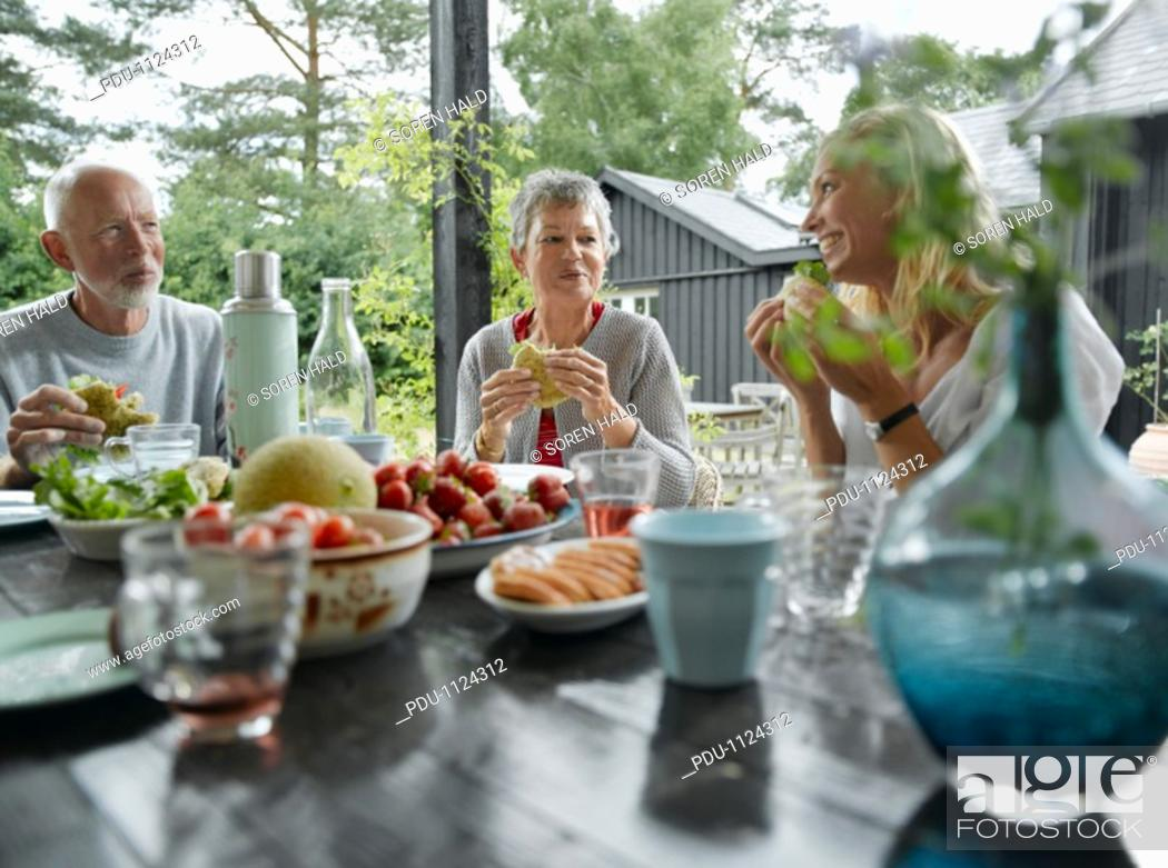 Stock Photo: Senior couple and daughter eating lunch on garden terrace, smiling.