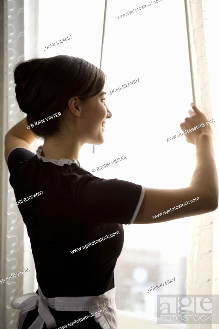 Stock Photo: Maid looking out window.