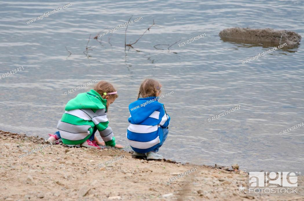 Stock Photo: Two children enthusiastically walk along the river bank.