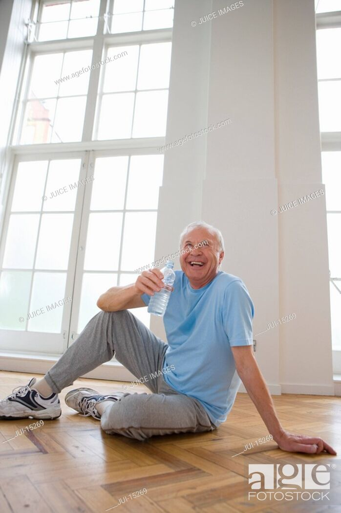 Stock Photo: Senior man with water bottle, smiling.