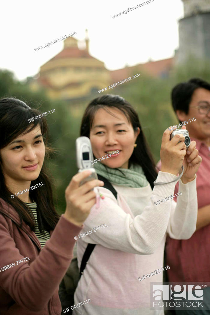 Stock Photo: Young Asian woman holding a mobile in her hand whereas an older looking woman is holding a camera, selective focus.