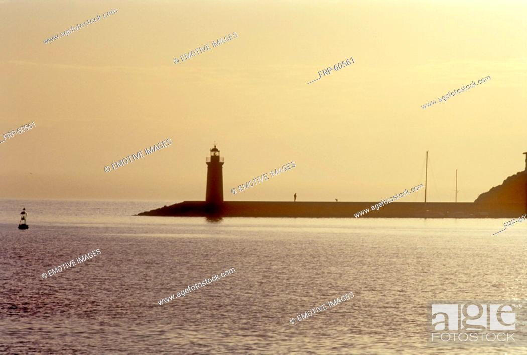 Stock Photo: At the sea: Lighthouse in sunset.