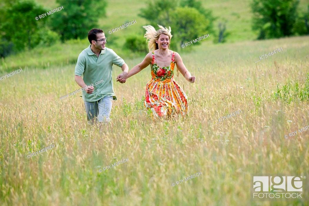Stock Photo: Running on top of hill in field.