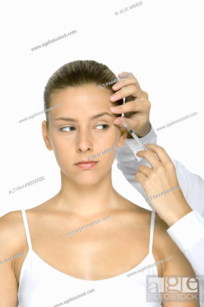 Stock Photo: Young woman receiving Botox injection.