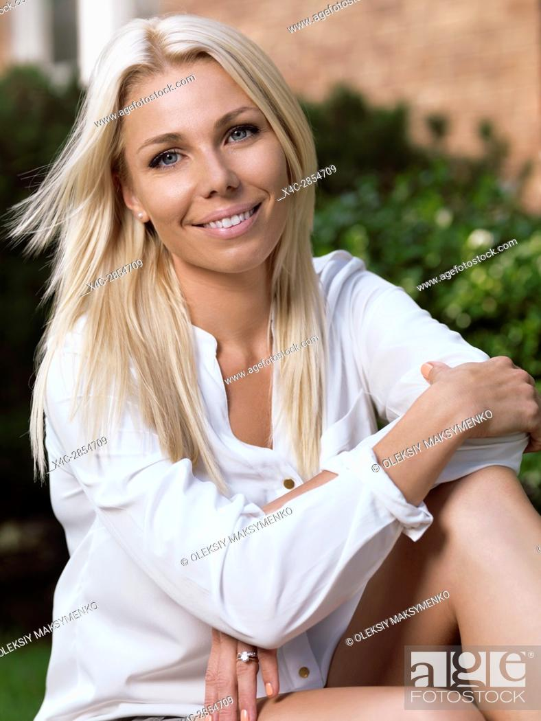 Stock Photo: Outdoor portrait of a young smiling caucasian woman with blond hair in her thirties sitting in front of a house.