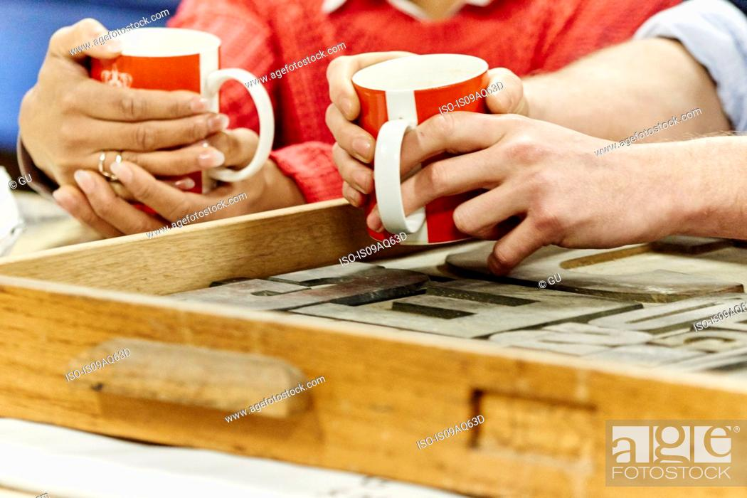 Stock Photo: Close up of male and female hands drinking coffee in traditional print workshop.