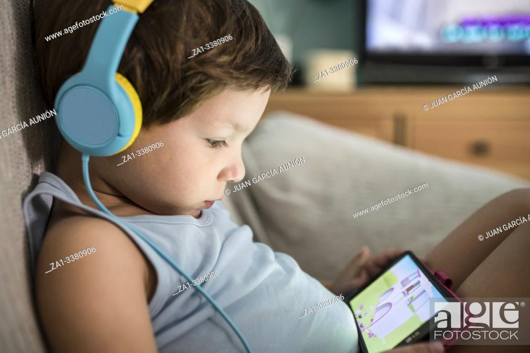 Stock Photo: Overstimulated children concept. Too Much Screen Time. 4 years boy in headphones watching videos while tv is working.