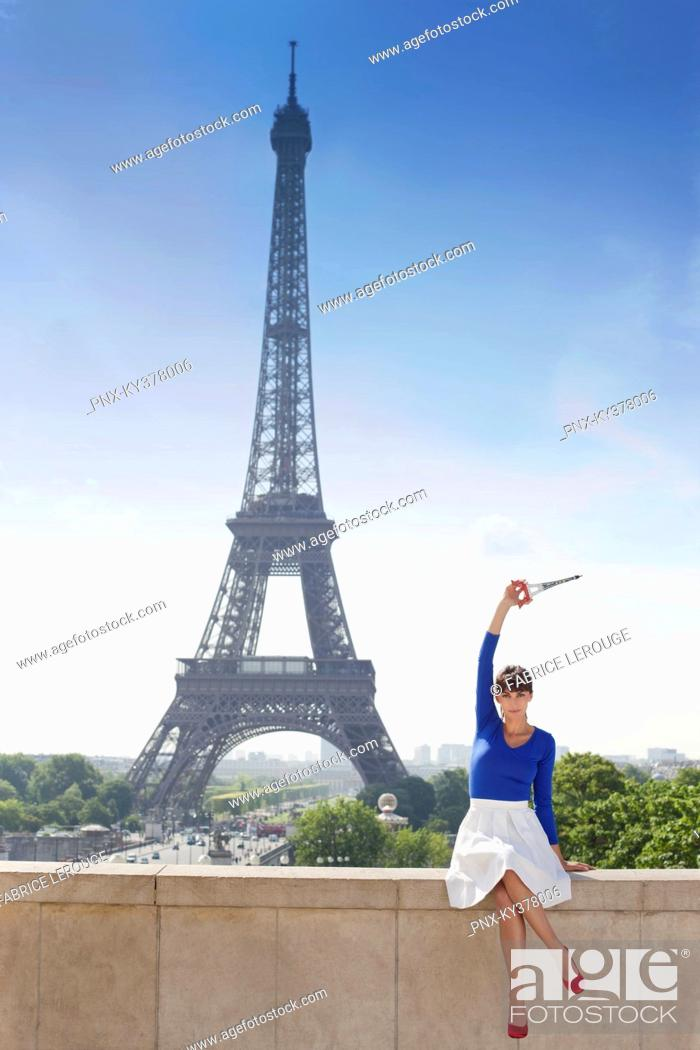 Stock Photo: Woman holding a replica of Eiffel Tower sitting on a stone wall with the Eiffel Tower in the background, Paris, Ile-de-France, France.