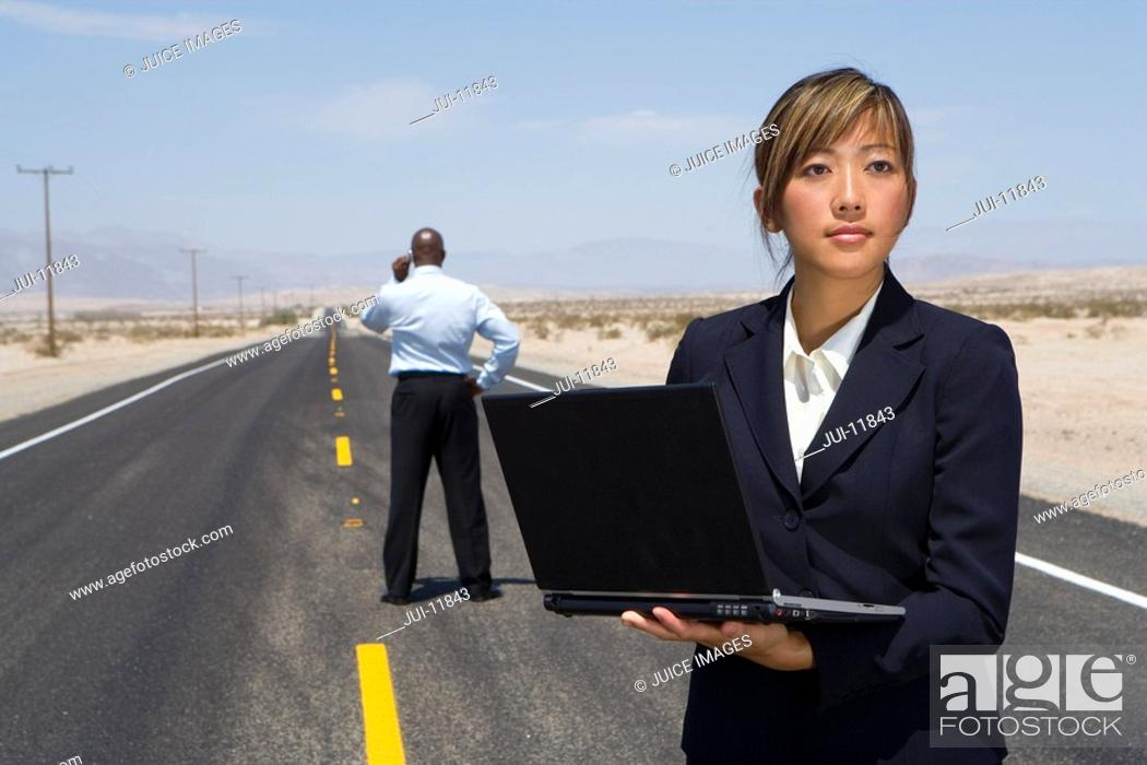 Stock Photo: Businesswoman in middle of road in desert using laptop computer, man in background.