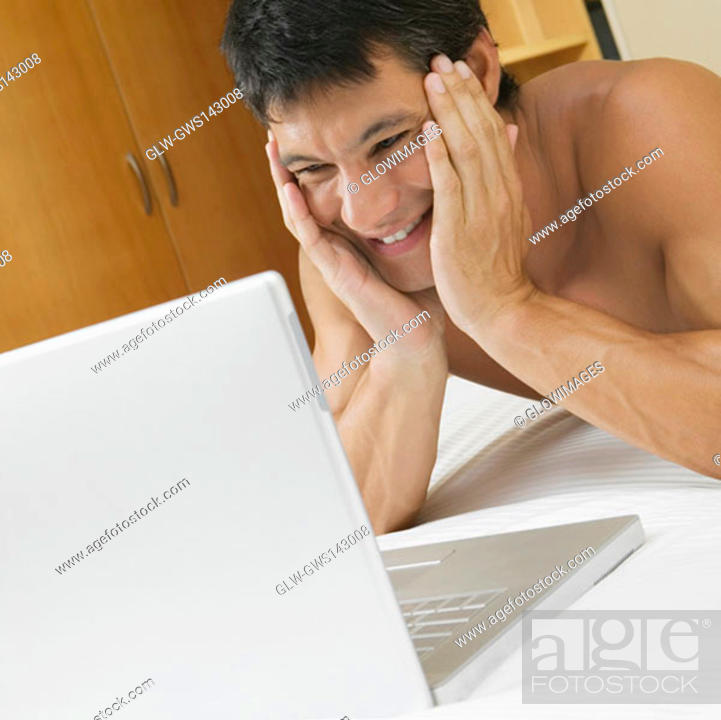 Stock Photo: Mid adult man lying on the bed with a laptop in front of him.