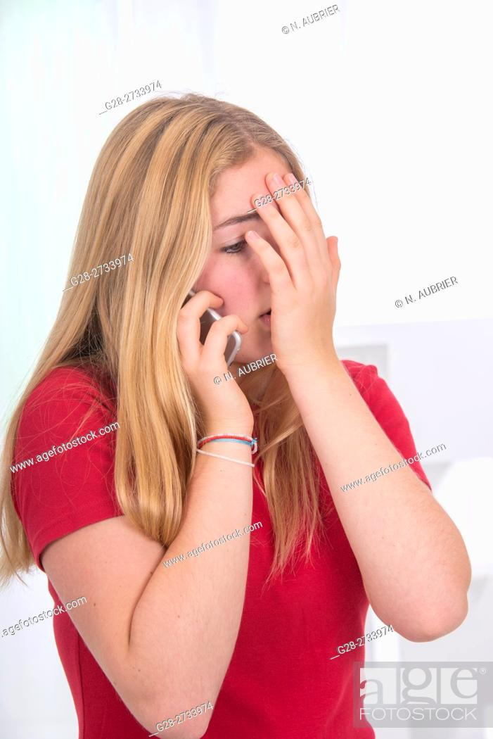 Stock Photo: Portrait of blond teenage girl holding her i-phone in one hand and hiding her face with the other hand in sign of embarrassment or pain, at home.