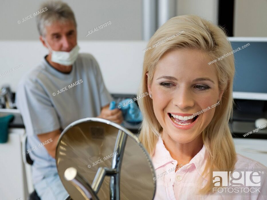 Stock Photo: Woman admiring smile in dentist's office.