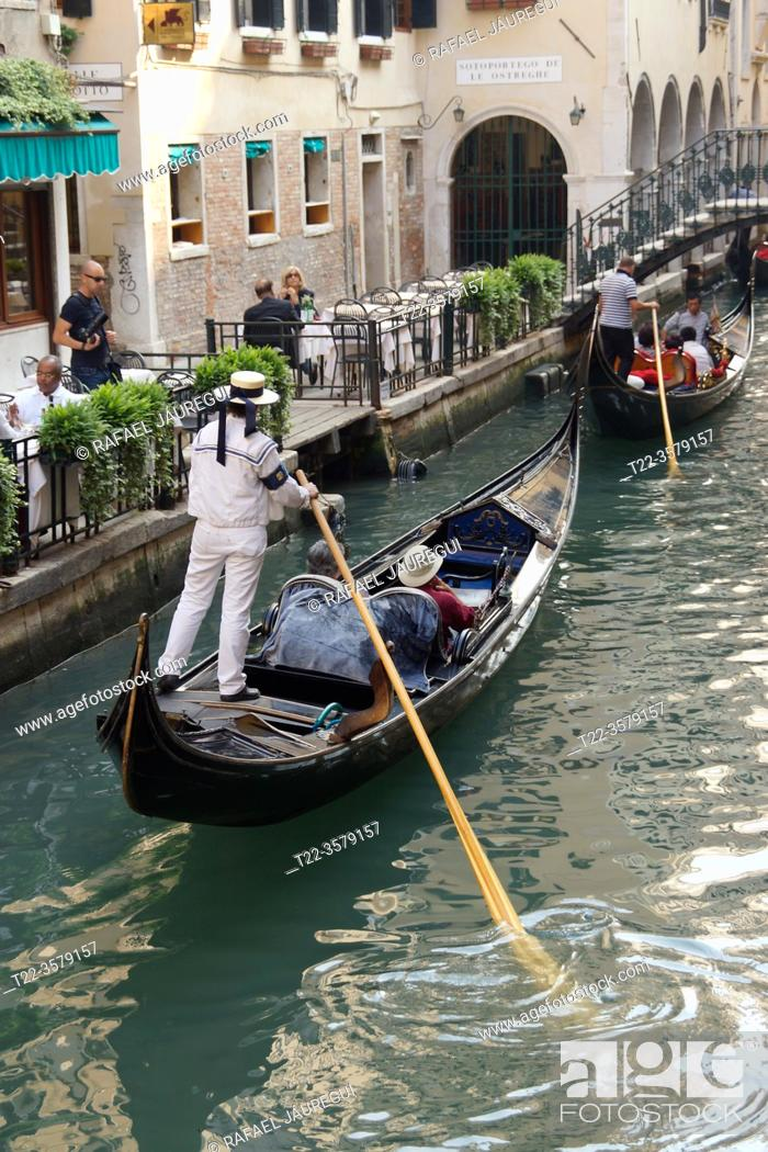 Stock Photo: Venice (Italy). Gondolier navigating one of the canals of the city of Venice.