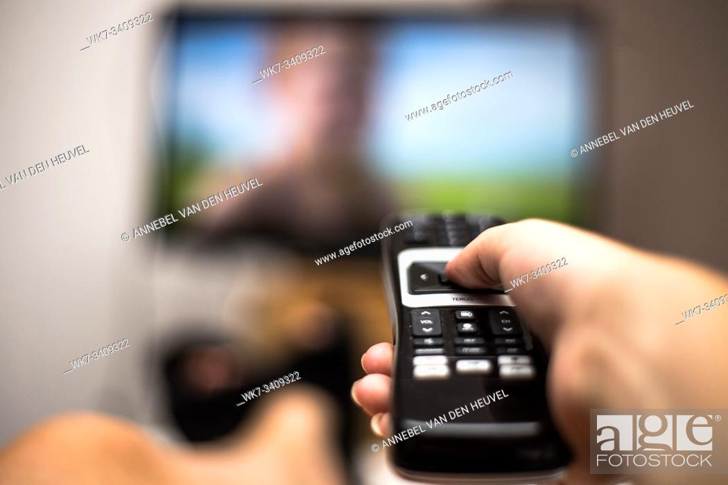 Stock Photo: Hand Holding Use Remote Control and Watching TV in House on a colorful flatscreen modern design.