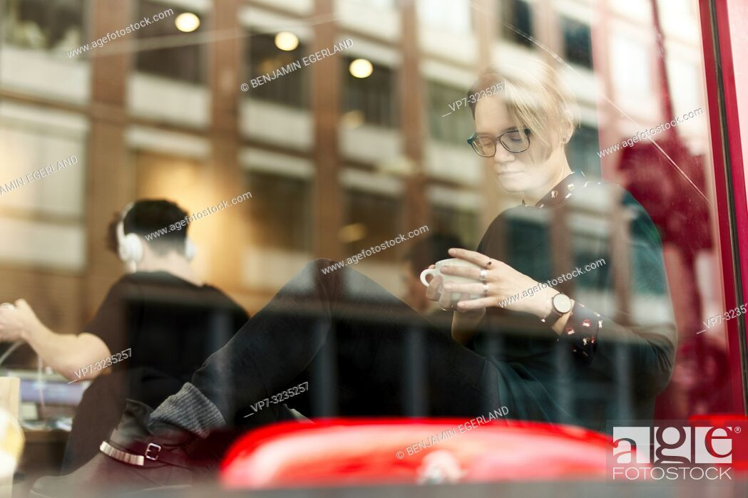 Stock Photo: woman behind glass window indoors in coffee shop, in Munich, Germany.