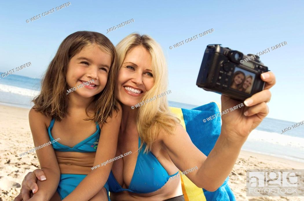 Stock Photo: Girl and mother photographing themselves on beach.